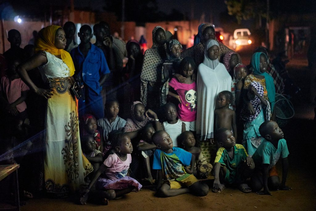 Community members in Niger watch a Mobile Cinema screening